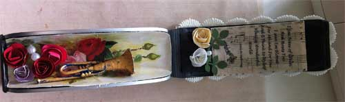 inside of altered eyeglass case with gold trumpet and roses